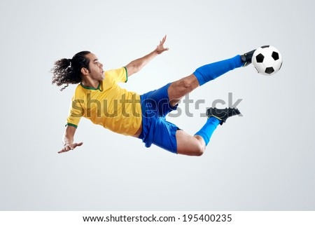 soccer player kicking ball towards goal for score and glory in brazil world cup - stock photo