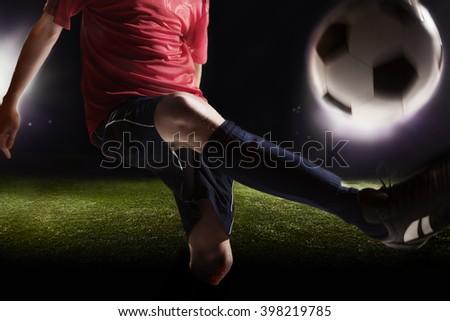 Soccer player kicking soccer ball - stock photo