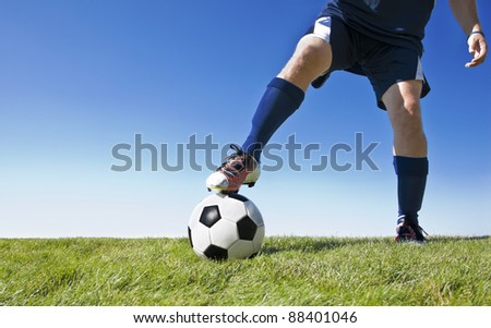 Soccer player kicking the ball during a game. - Lots of copy space - stock photo