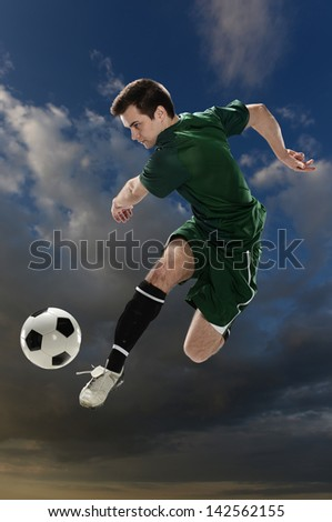 Soccer player kicking the ball with clouds on a the background