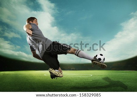 Soccer player kicking the soccer ball in mid air - stock photo