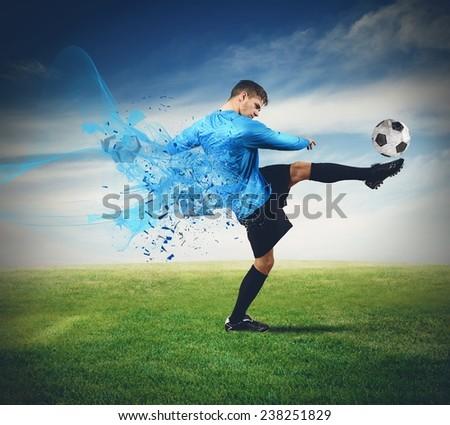 Soccer player kicks ball in a field - stock photo