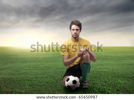 Soccer player kneeling on a green meadow