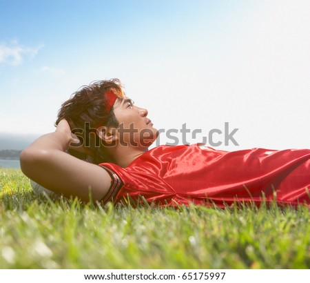 Soccer player lay in grass resting head on ball - stock photo
