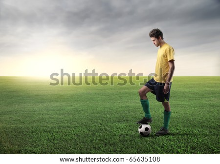 Soccer player on a green meadow - stock photo
