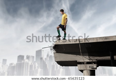 Soccer player on the edge of a broken bridge - stock photo