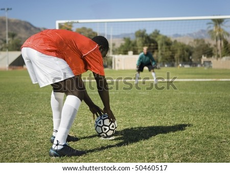 Soccer player preparing for penalty kick, back view - stock photo
