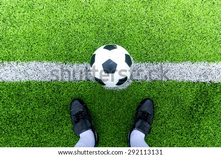 Soccer player ready to play at kick off point in soccer field.  - stock photo