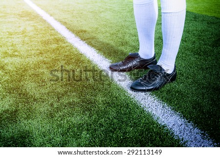 Soccer player ready to play at white line in soccer field. - stock photo