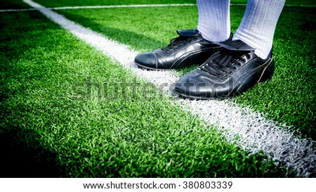 Soccer player ready to play at white line in soccer field.