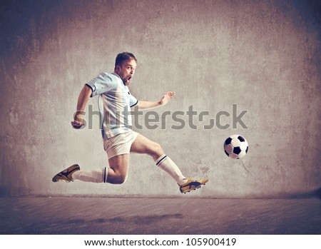 Soccer player running after a football - stock photo
