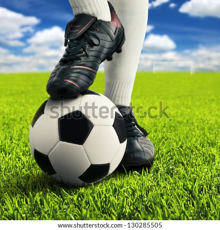 Soccer player's feet in casual pose on an open playing field, with sky in background - stock photo
