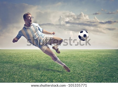 Soccer player shooting a ball on a football court - stock photo