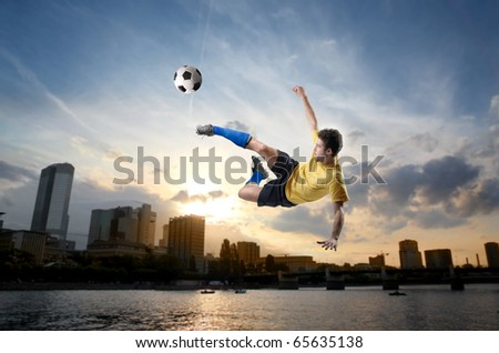 Soccer player shooting a football with cityscape on the background - stock photo