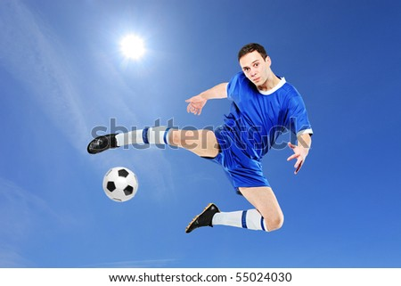 Soccer player with a ball in action against blue sky - stock photo