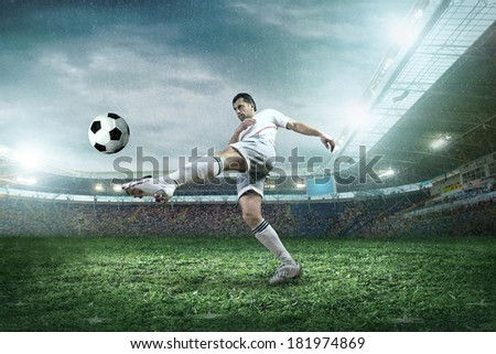 Soccer player with ball in action in rain. - stock photo
