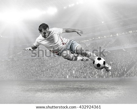 Soccer player with ball in action on field of stadium - stock photo