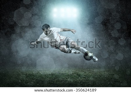 Soccer player with ball in action outdoors - stock photo