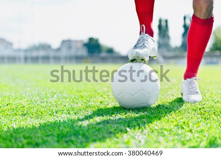 Soccer player with ball on a playing field - stock photo
