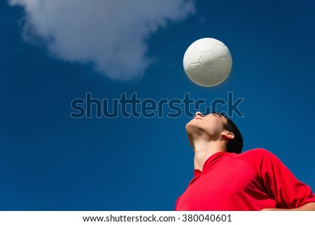 Soccer player with ball. Sky as background, convenient space for copy - stock photo