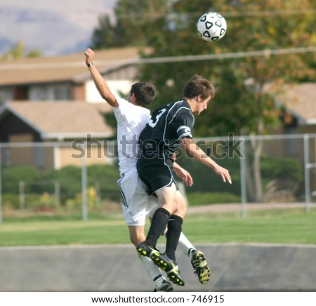 Soccer players collide while trying to bring down the ball - stock photo