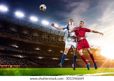 Soccer players in action on sunset stadium background panorama - stock photo