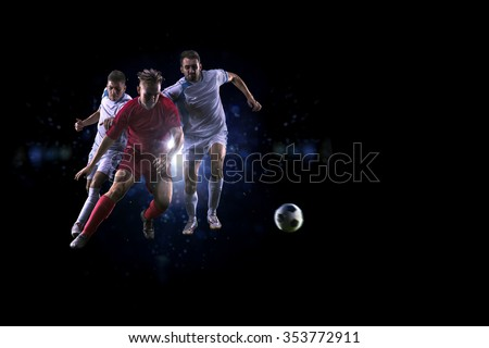 Soccer players in action over black background - stock photo