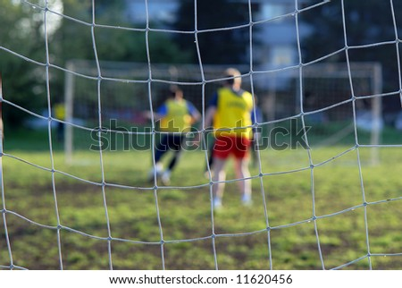 Soccer players in front of net, close-up focus on net - stock photo