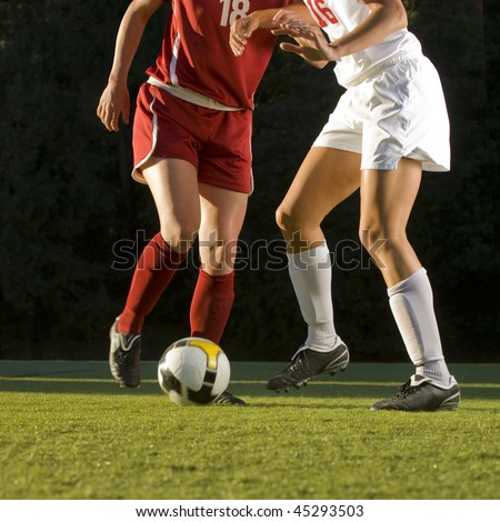 Soccer players with ball and feet kicking on field