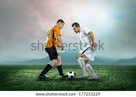 Soccer players with ball in action outdoors. - stock photo