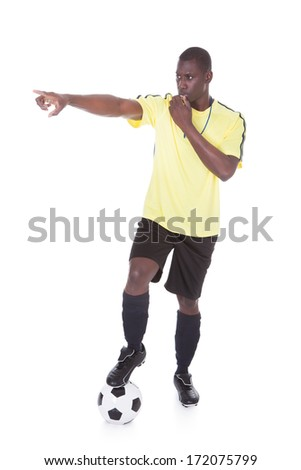 Soccer Referee Blowing Whistle With Leg On Ball Over White Background - stock photo