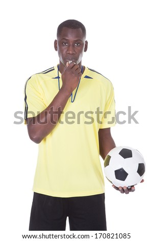 Soccer Referee Holding A Ball With A Whistle In His Mouth - stock photo