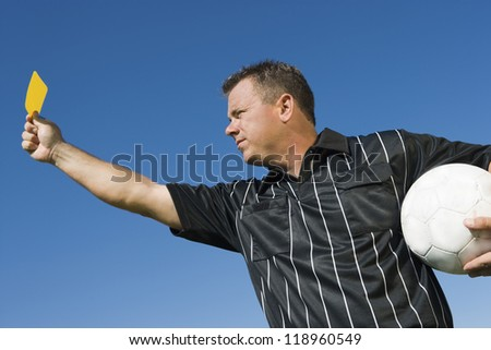 Soccer Referee Holding Yellow Card - stock photo