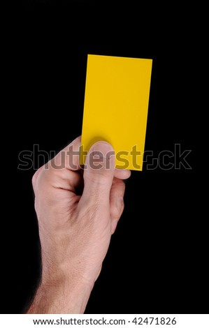 Soccer referee is holding a yellow card, isolated on black - stock photo