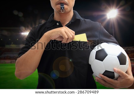 soccer referee showing a yellow card in stadium - stock photo