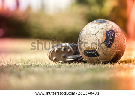 Soccer shoes & football on the green grass-Filtered Image - stock photo