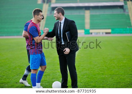 soccer  sport manager in business suit coach and football player on stadium with green grass and white ball - stock photo