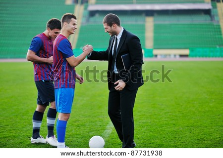 soccer  sport manager in business suit coach and football player on stadium with green grass and white ball