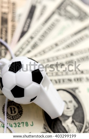 soccer whistle on dollar notes, concept sport bets, or corruption