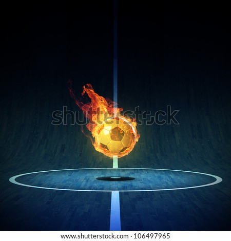 Soccerball on Fire or burning Soccerball on indoor soccer field - stock photo