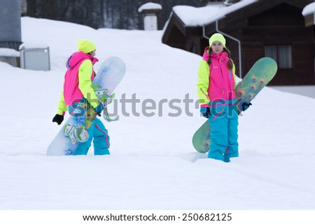 SOCHI, RUSSIA - FEBRUARY 26, 2014: Two unidentified girls go with snowboards in hand at the ski resort. - stock photo