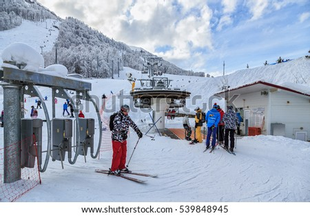 Sochi, Russia - January 9, 2015: A skier has passed a turnstile for boarding onto a chair ski lift in Gorky Gorod winter mountain ski resort. Skiers queue up for a ski lift ride