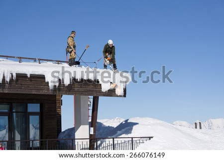 SOCHI, RUSSIA - JANUARY 22, 2015: Industrial climbers take off the snow and icicles from the roof - stock photo