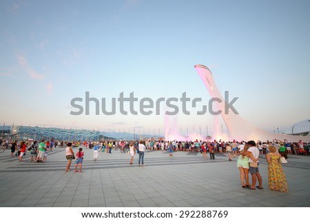 SOCHI, RUSSIA - JUL 27, 2014: Crowds of tourists in the Olympic park with a bowl of the Olympic flame and singing Fountain in the evening - stock photo