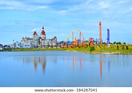 """SOCHI, RUSSIA - March 28, 2014: Roller coasters at the amusement park """"SochiPark and the """"Bogatyr"""" hotel"""". Built for the Olympic Games 2014 - stock photo"""