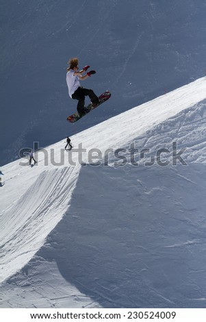 SOCHI, RUSSIA - MARCH 22, 2014: Snowboarder jumps in Snow Park,  mountain ski resort Rosa Khutor. - stock photo