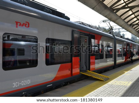 """SOCHI, RUSSIA - March 8, 2014: Suburban train Lastochka (""""Swallow""""), equipped with a ramp for wheelchair users arrival at the station Sochi - stock photo"""