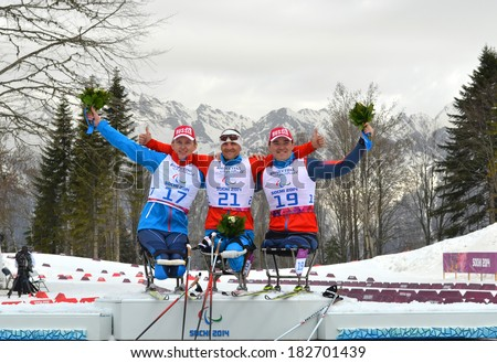 SOCHI, RUSSIA - March 9, 2014: Winners Alexander Davidovich, Irek Zaripov and Roman Petushkov (all athletes from Russia) during flower ceremony on Winter Paralympic Games  in Sochi.  - stock photo
