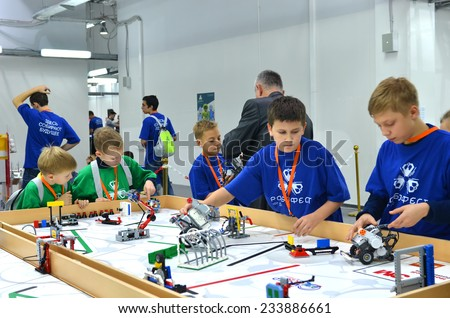 SOCHI, RUSSIA - November 21, 2014: Schoolchildren Team Russia with many robots on the playing field during Robofest on World Robot Olympiad Russia 2014. It was attended by delegates from 47 countries - stock photo