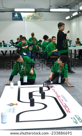 SOCHI, RUSSIA - November 21, 2014: Schoolchildren with robot on the playing field during Robofest, a part of World Robot Olympiad Russia 2014. It was attended by delegates from 47 countries - stock photo